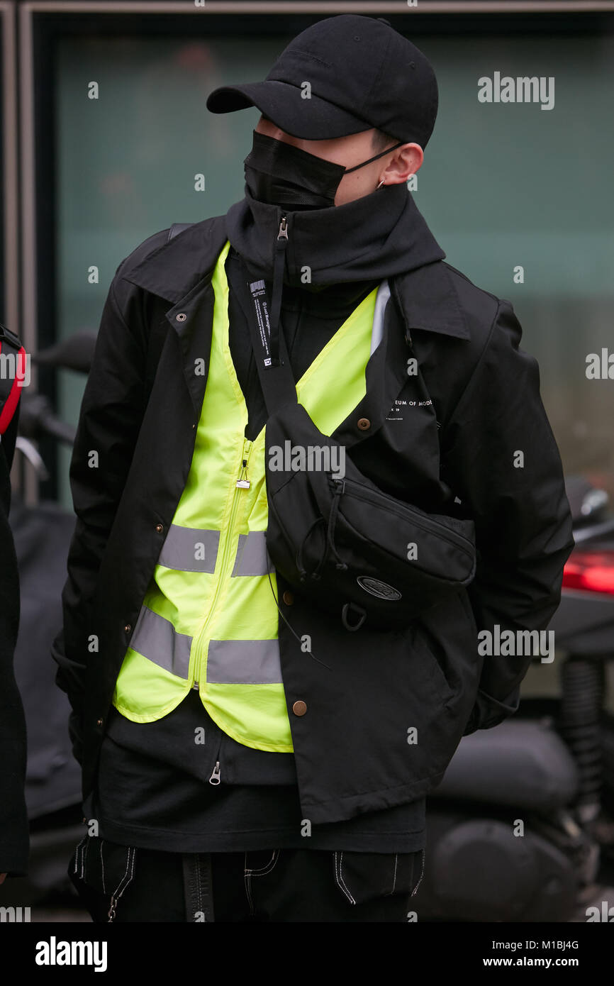 MILAN - JANUARY 15: Man in black with yellow jacket and black pollution mask before Giorgio Armani fashion show, - Stock Image