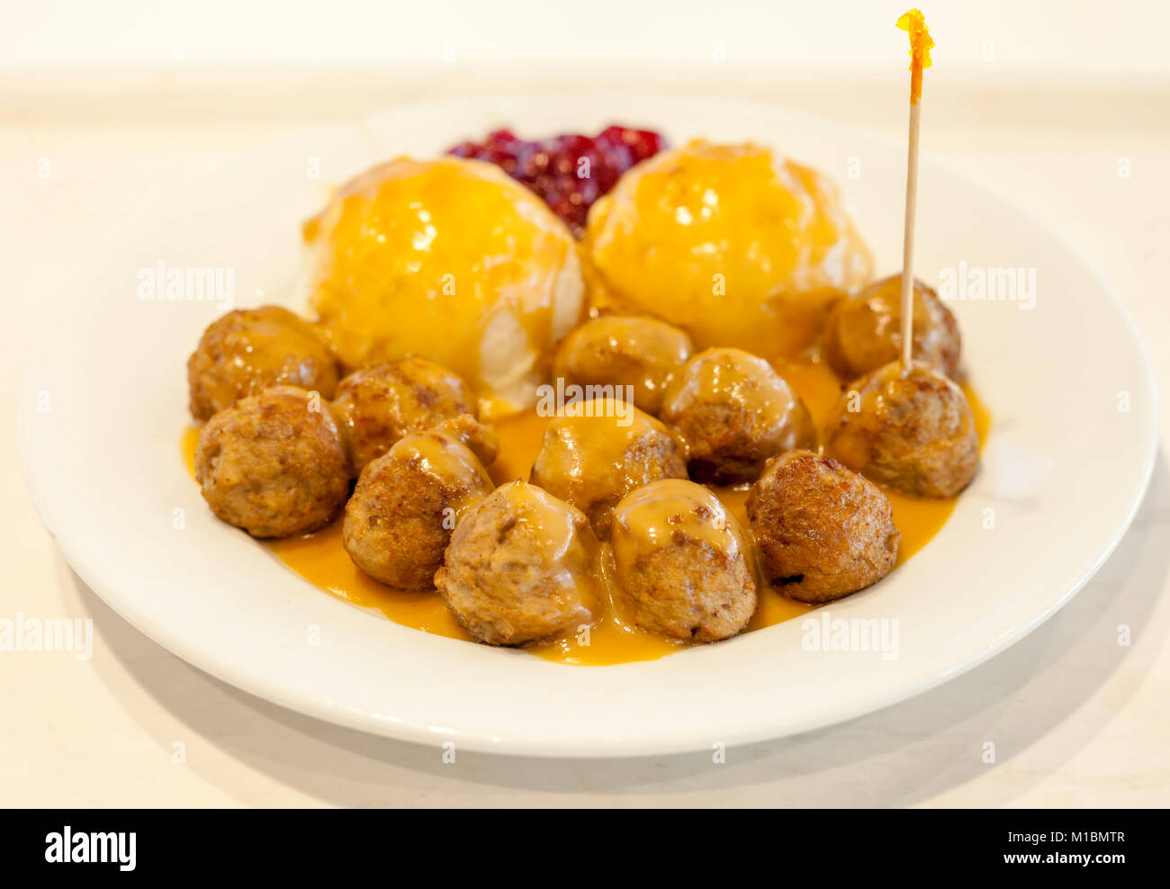 Plate of swedish meatballs with gravy and side of mash potatoes and lingonberry jam - Stock Image