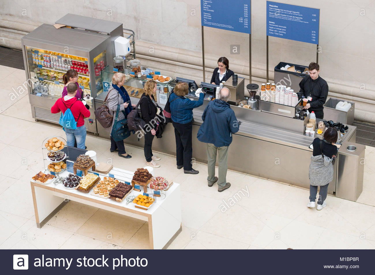 People standing in line to purchase drinks and snacks at the Court Café in the Queen Elizabeth II Great Court covered Stock Photo