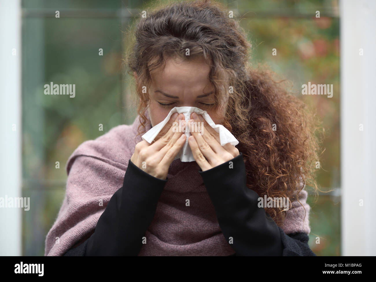 Symbol picture for cold, flu, disease, portrait of a woman blowing her nose in paper tissue - Stock Image