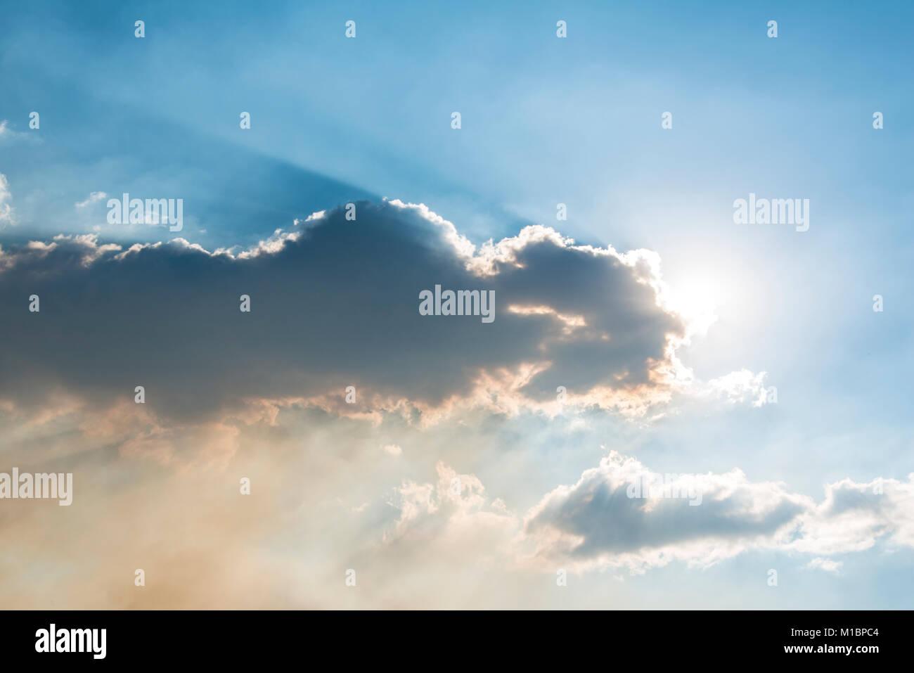 Sun shines behind dark cloud, California, USA - Stock Image