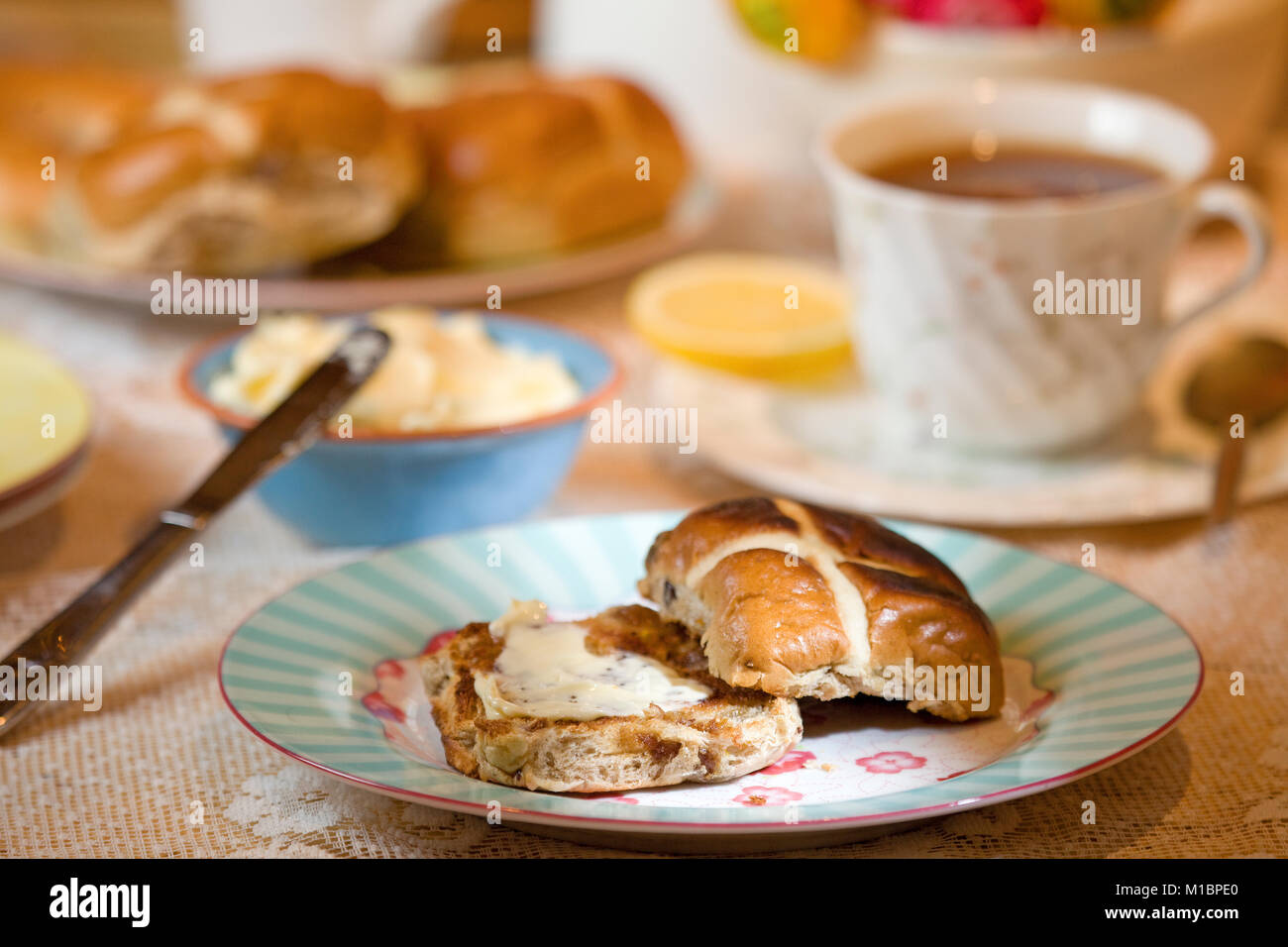 Toasted Hot Cross Bun with melted butter - Stock Image