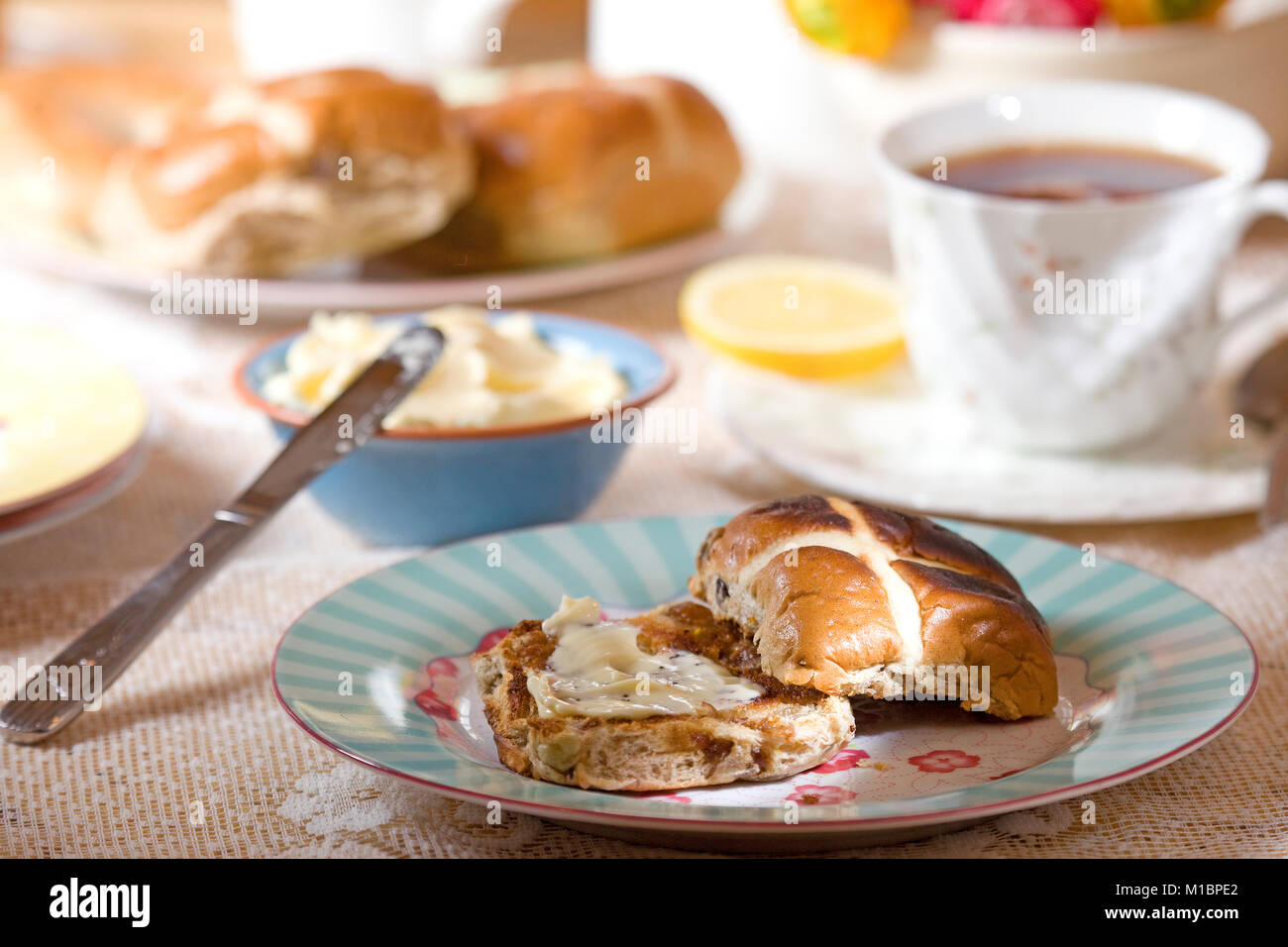 Fresh Hot Cross Buns with melted butter - Stock Image