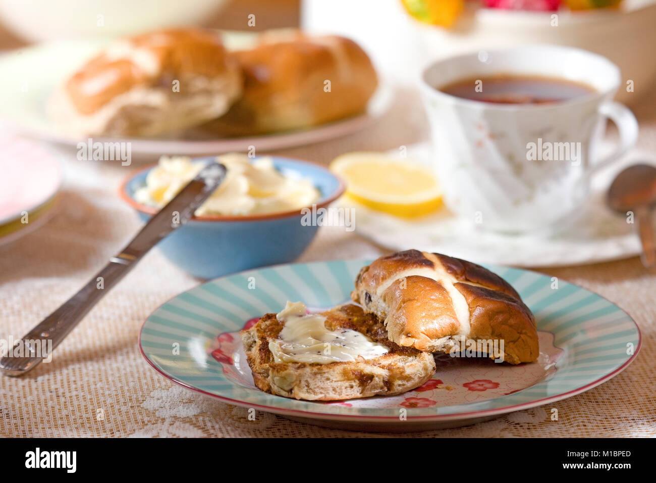 Hot cross buns with melted butter - Stock Image
