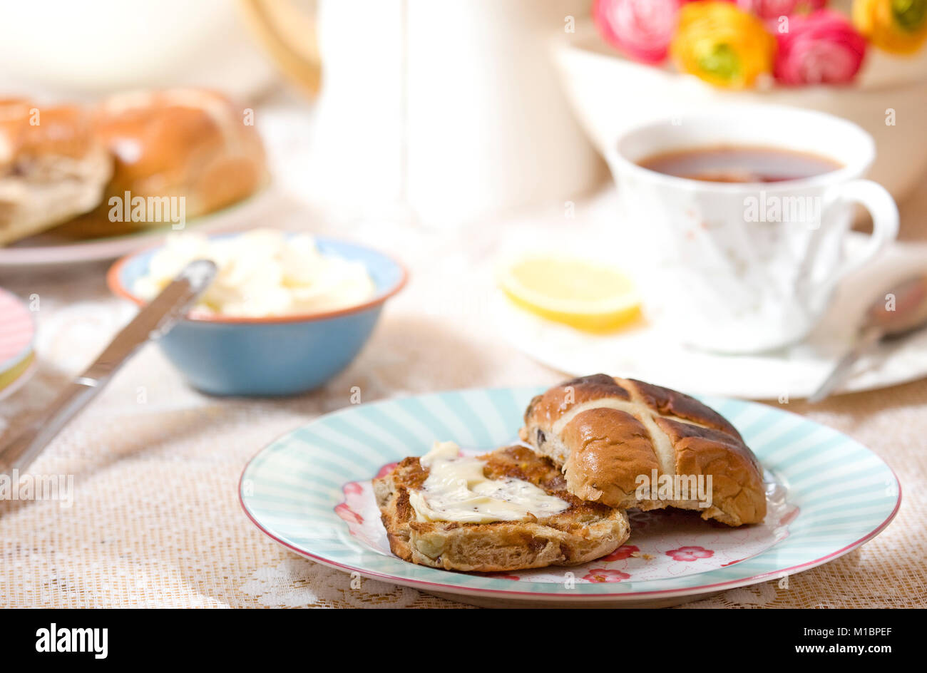 fresh hot cross bun with melted butter - Stock Image