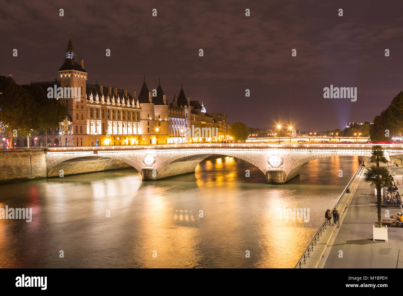Conciergerie and Pont au Change on the banks of the Seine at night, Île de la Cité, Paris, France - Stock Image