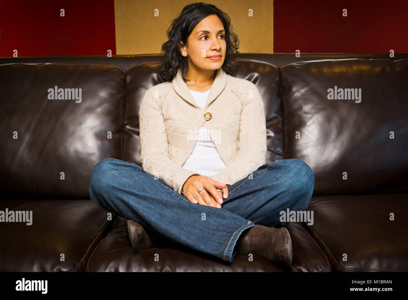 Portrait of a young Sri- Lanken American woman seated on a couch and looking off to the side. - Stock Image