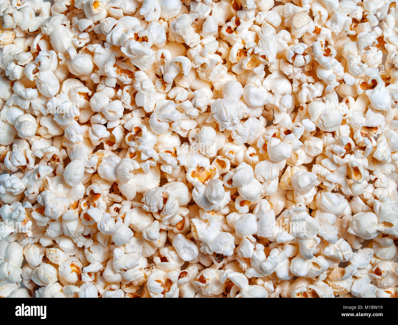 Ready popcorn of corn grains textural background close-up on top - Stock Image