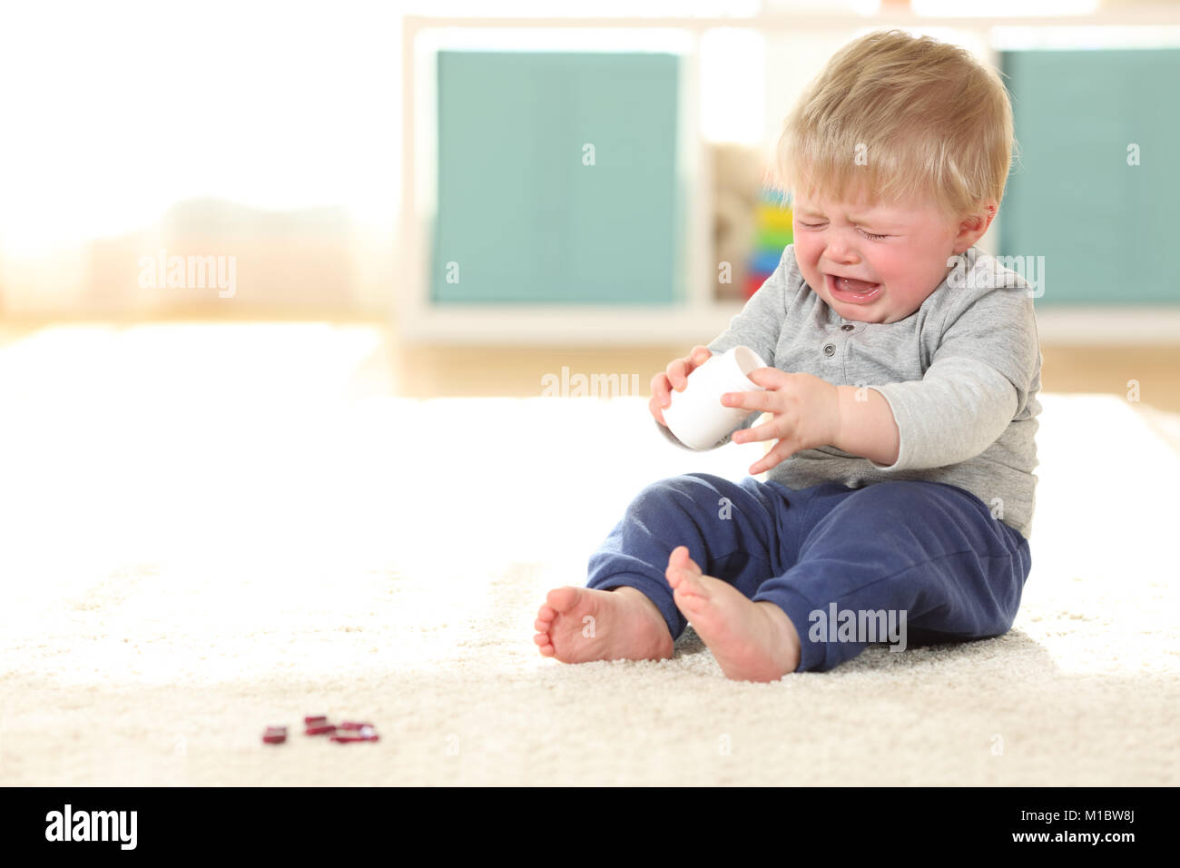 Sad Baby Crying In Danger After Eating Some Pills From A Bottle On The  Floor At Home