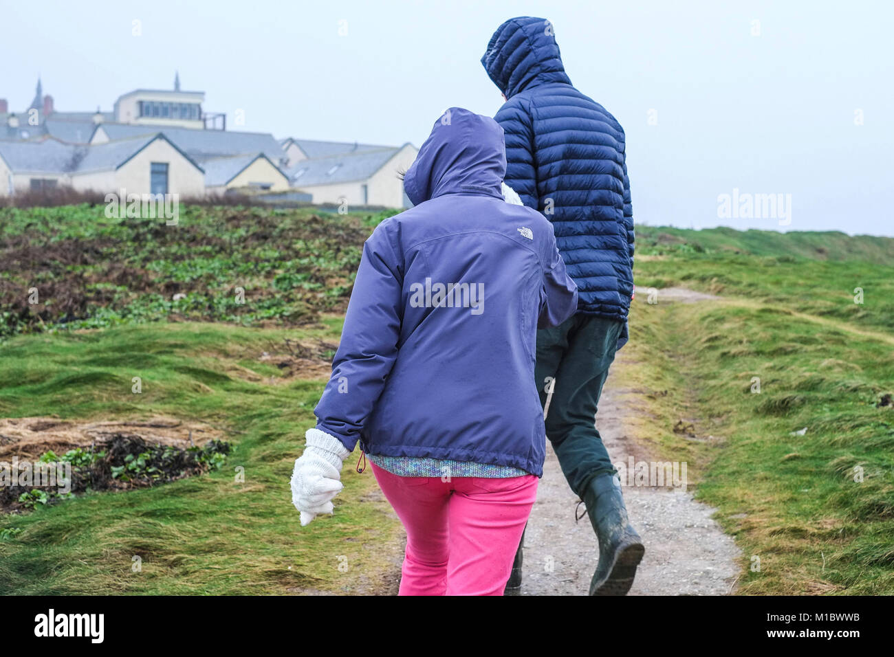 UK Winter weather - Two people walkers struggling to walk against high winds on the Newquay coast Cornwall. - Stock Image