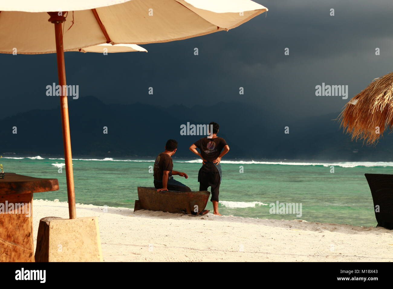 A pair of waiters watch the storm hitting a neighboring island and consider if it's worth bringing the bean - Stock Image