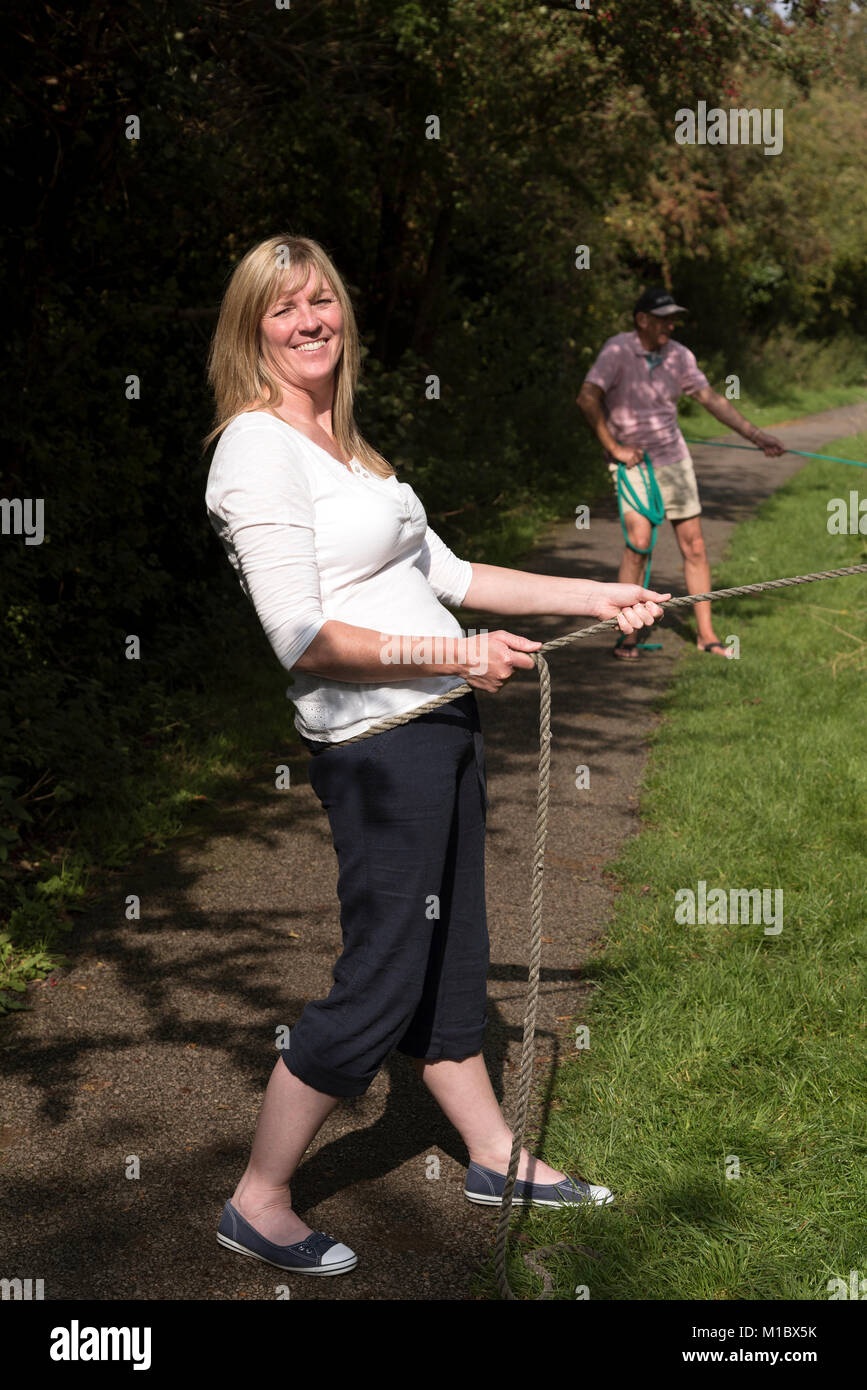 Holidaymaker standing on towpath pulling the mooring line of a narrowboat during a holiday afloat - Stock Image