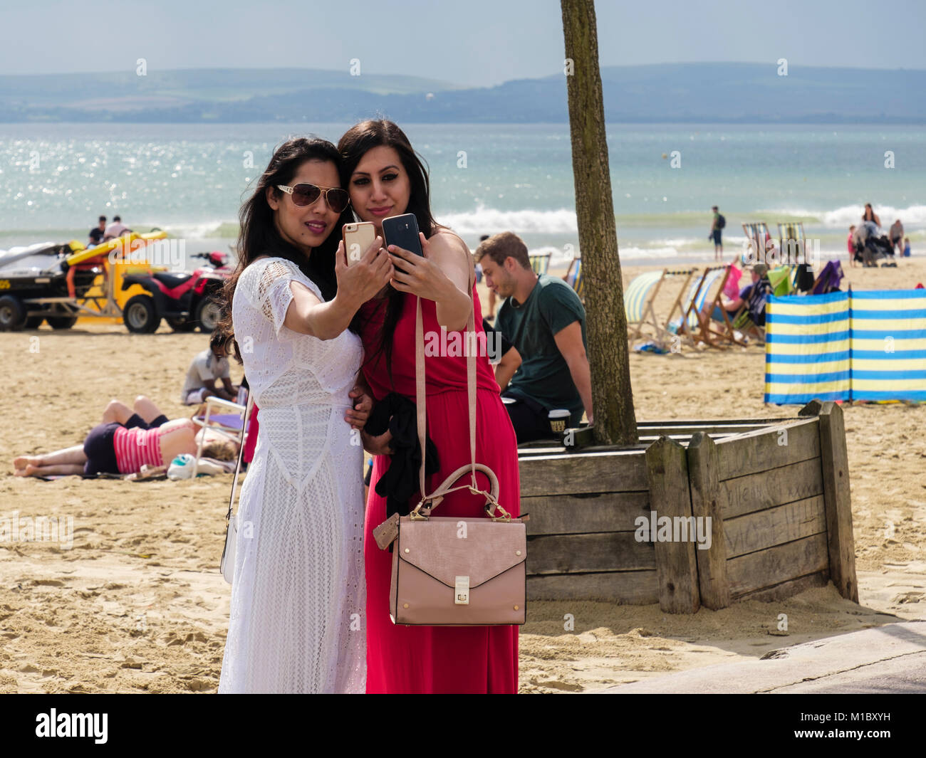 Two smartly dressed young millennial women taking selfies together using smartphones on a beach in late summer. Stock Photo