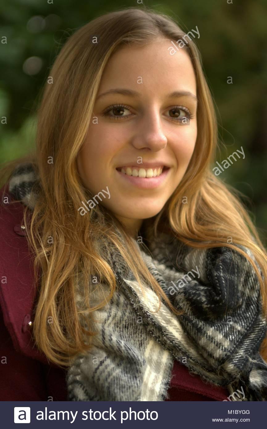 Herbstliches Portrait einer attraktiven jungen Frau mit dunkelblonden, langen Haaren, dunkelroter Jacke und Schal - Stock Image