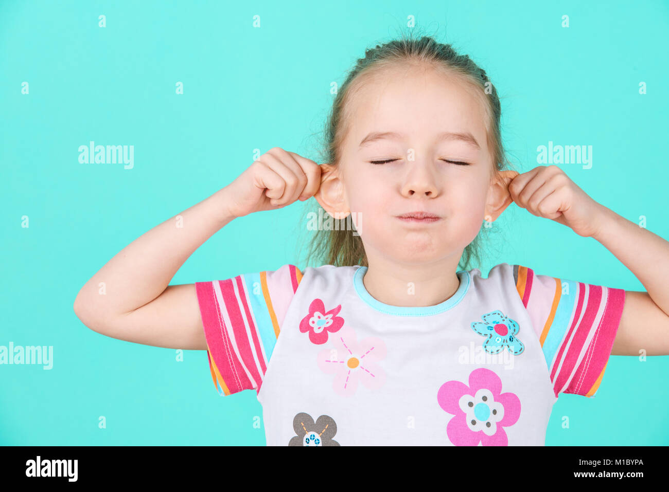 Adorable little girl making funny face. Grimacing concept. Stock Photo