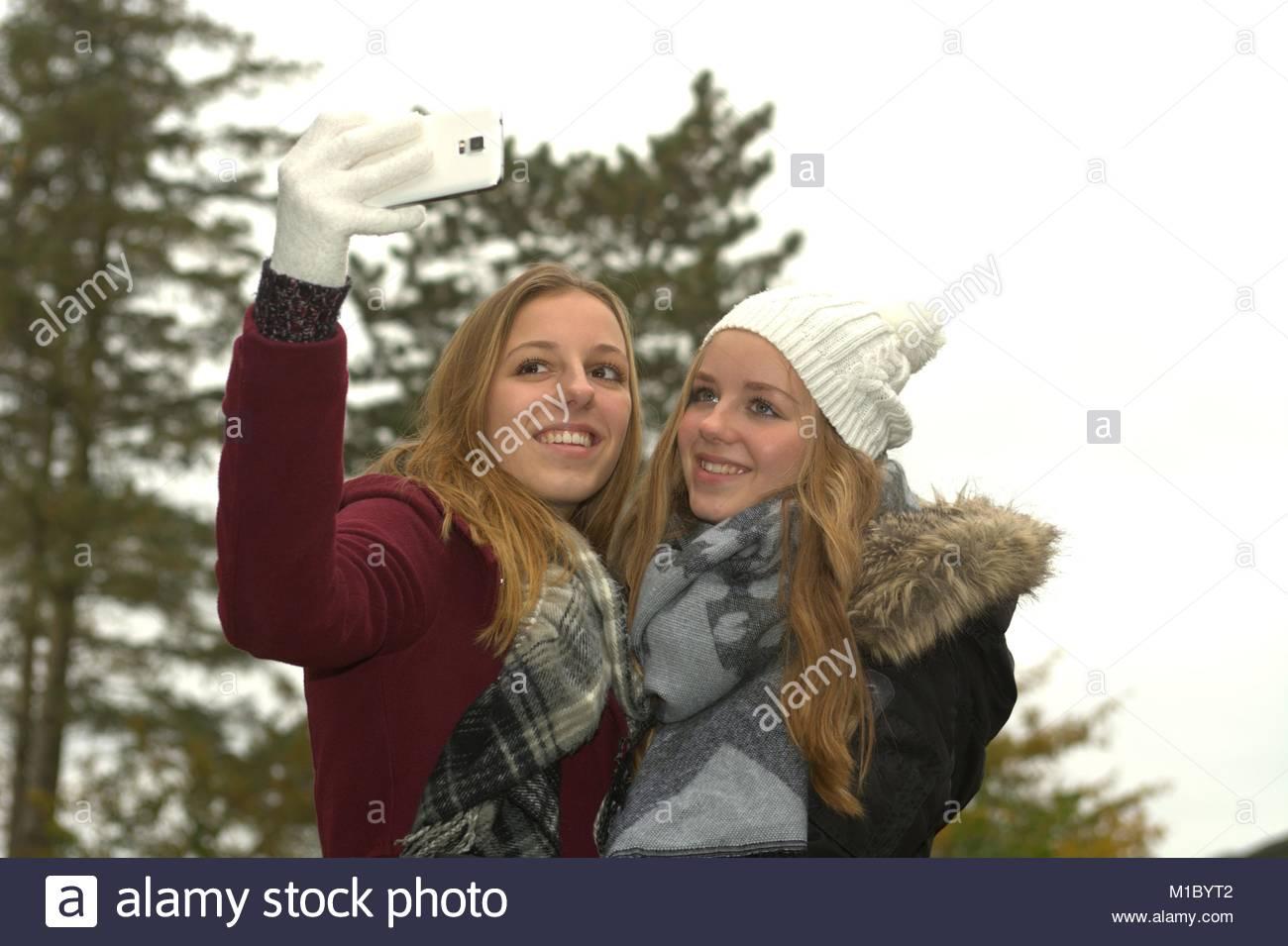 Zwei froehliche Teenager Maedchen machen mit dem Smartphone ein gemeinsames Selfie in der herbstlichen Natur. Stock Photo
