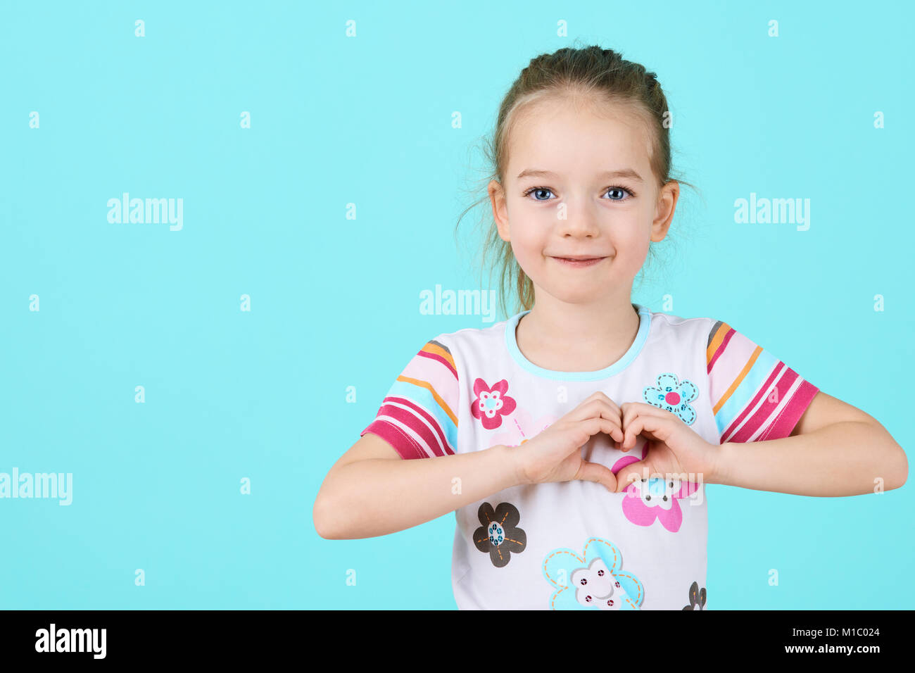 Children, Charity, Healthcare, Adoption Concept. Smiling little girl making heart-shape gesture over candy blue - Stock Image