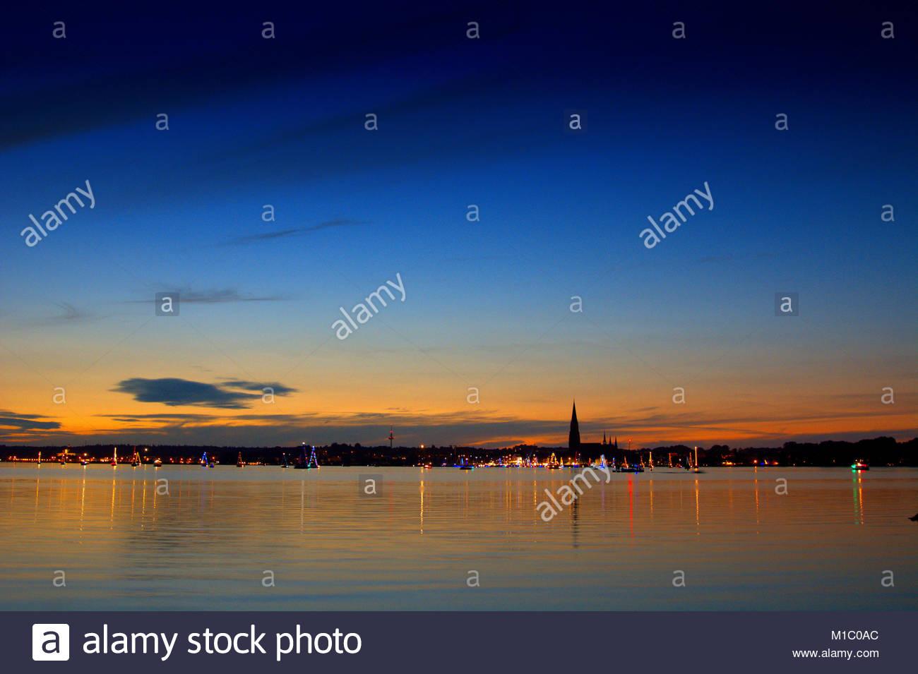 Die Skyline von Schleswig mit einem traumhaften Abendhimmel an einem schoenen Spaetsommerabend. Auf dem Wasser fahren - Stock Image