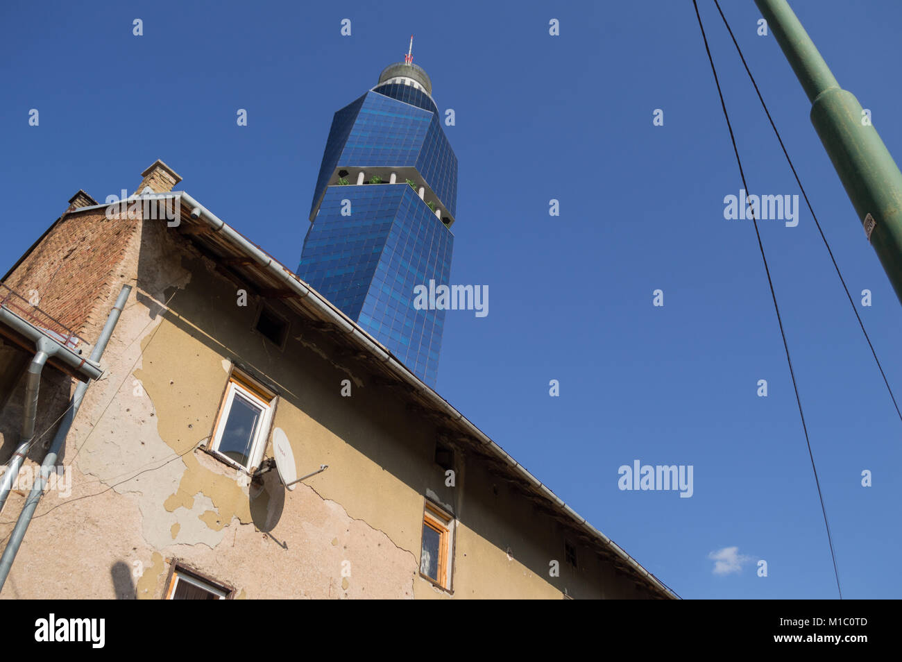 Avaz Twist Tower and Traditional Houses with Bullet Hole Remains in Sarajevo, Bosnia and Herzegovina - Stock Image