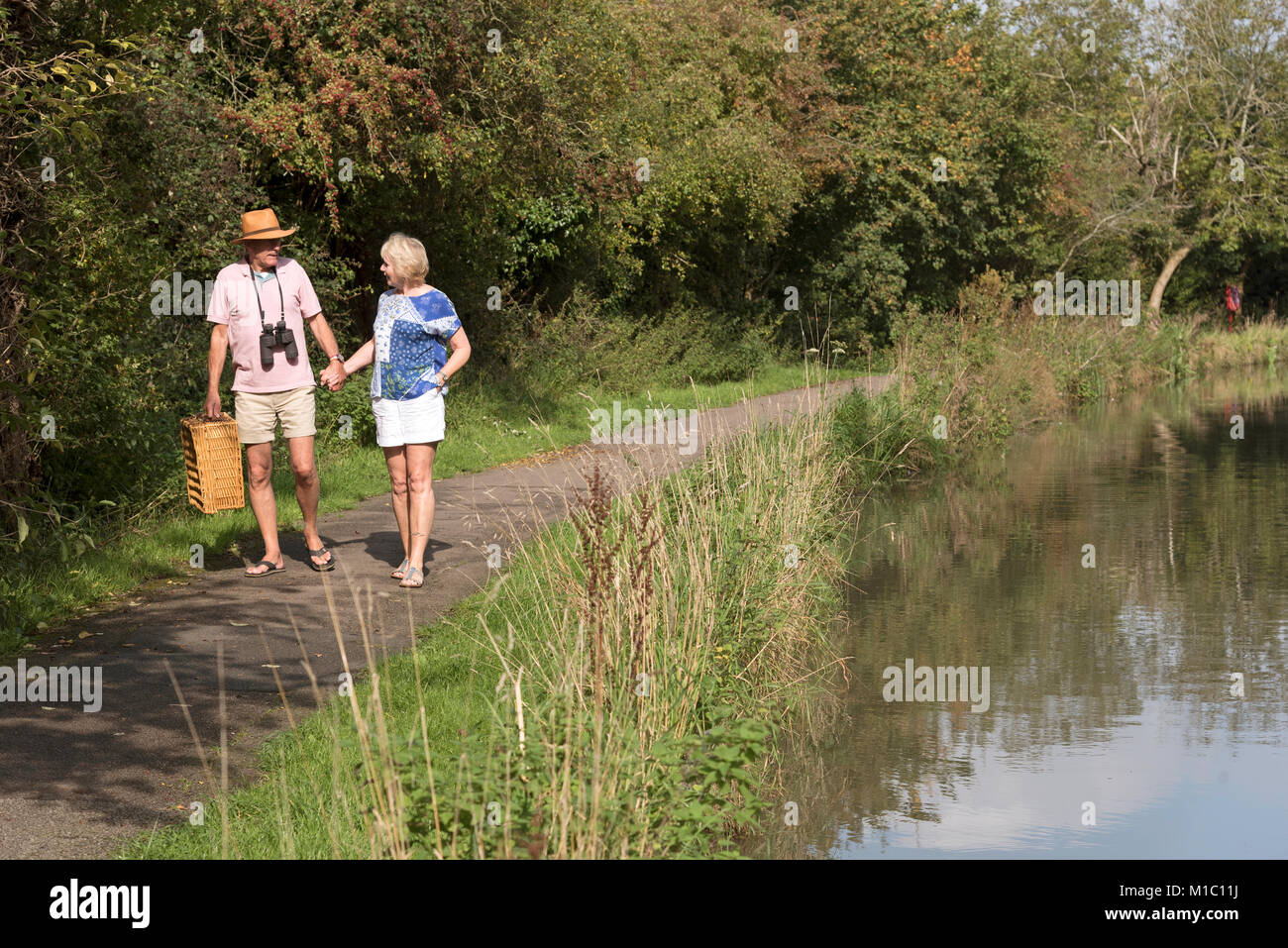 Couple carrying a picnic basket walking along a towpath next to the river - Stock Image