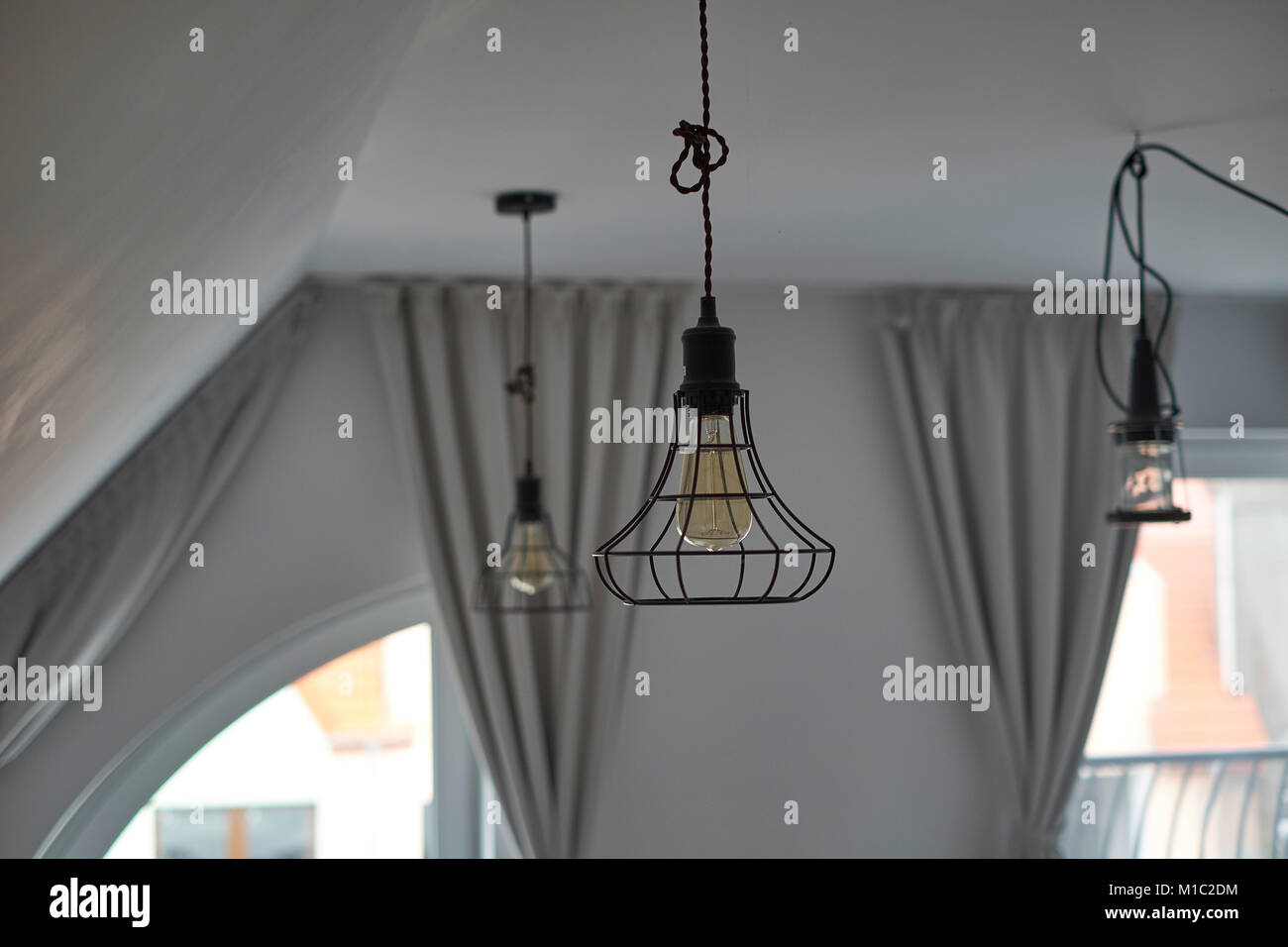 Industrial wire pendant lamps in loft living room Stock Photo ...