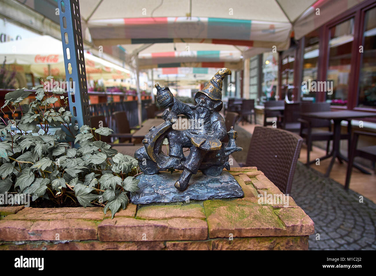 Tourist attraction statues of Wroclaw's dwarfs. Old gnome drinking ale. Stock Photo