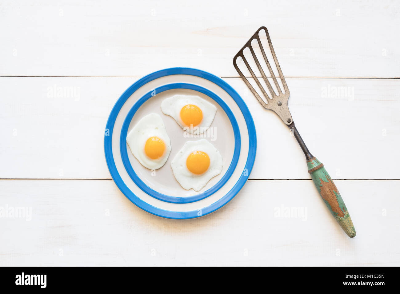 Fried Quail Eggs on a cornishware plate with a vintage spatula from above Stock Photo