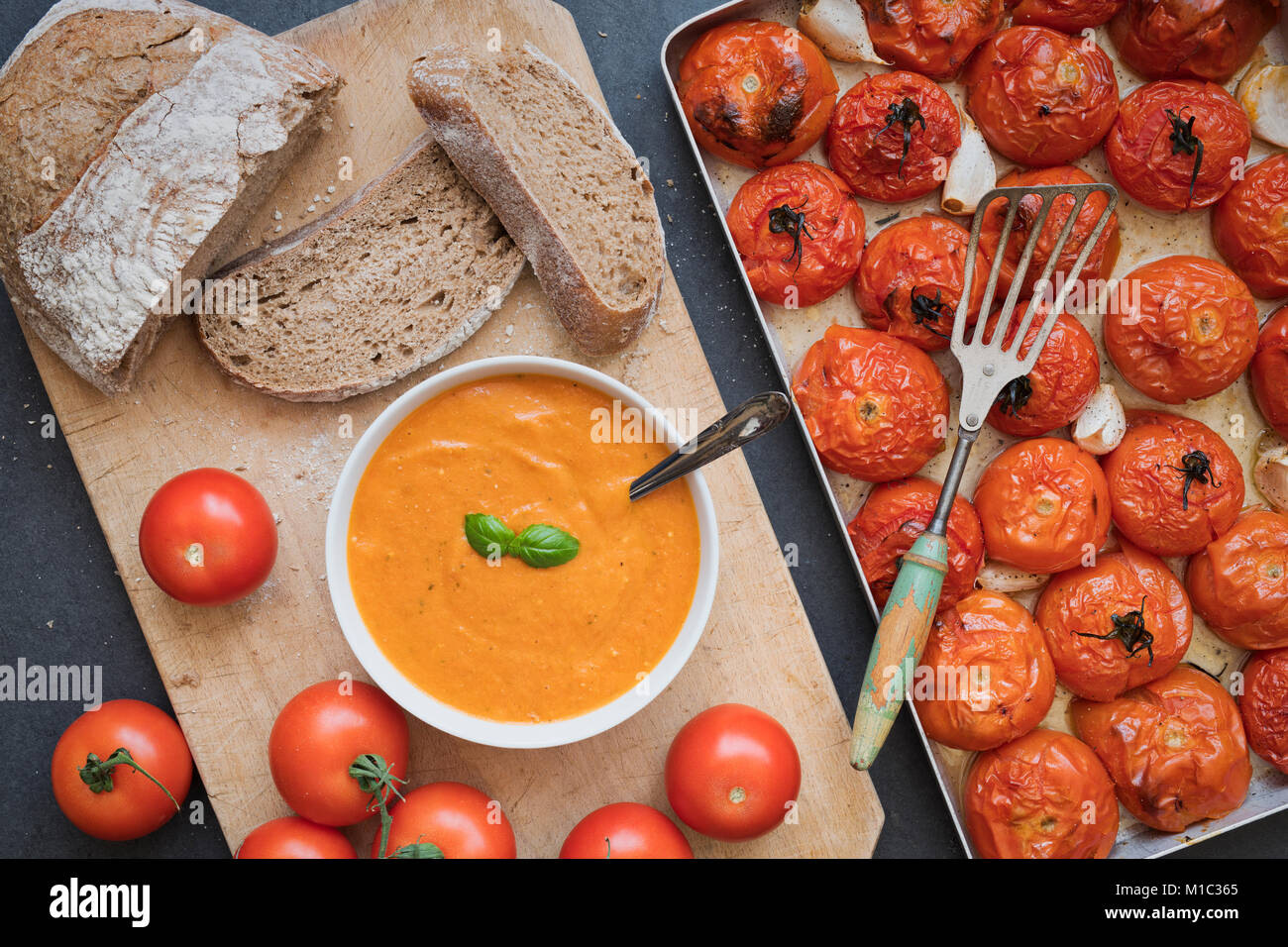 Homemade tomato and basil soup with rye bread next to roasted tomatoes and garlic in a baking tray on a slate background. - Stock Image