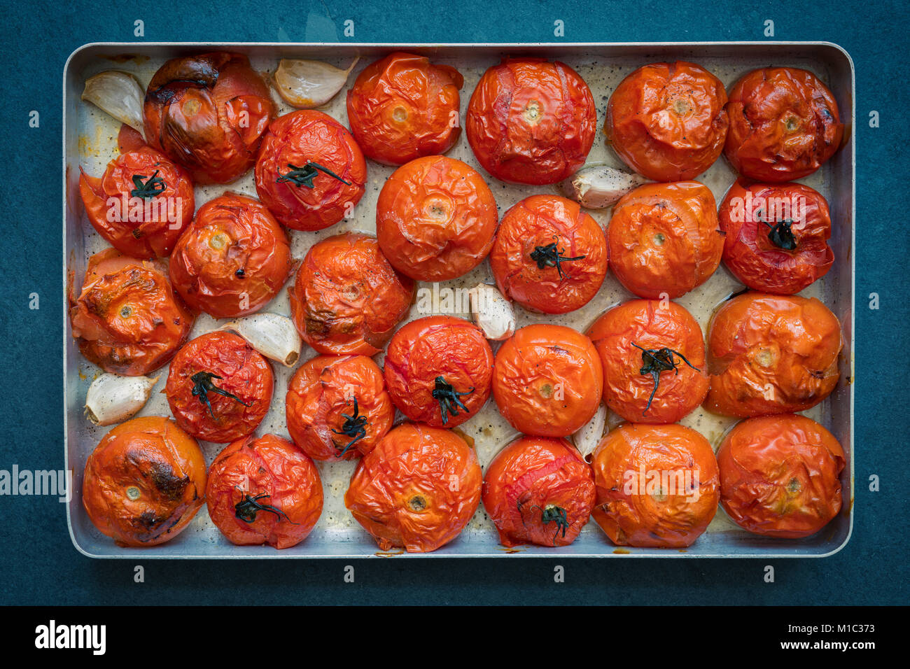 Roasted tomatoes and garlic in a baking tray on a slate background. Vintage filter applied - Stock Image