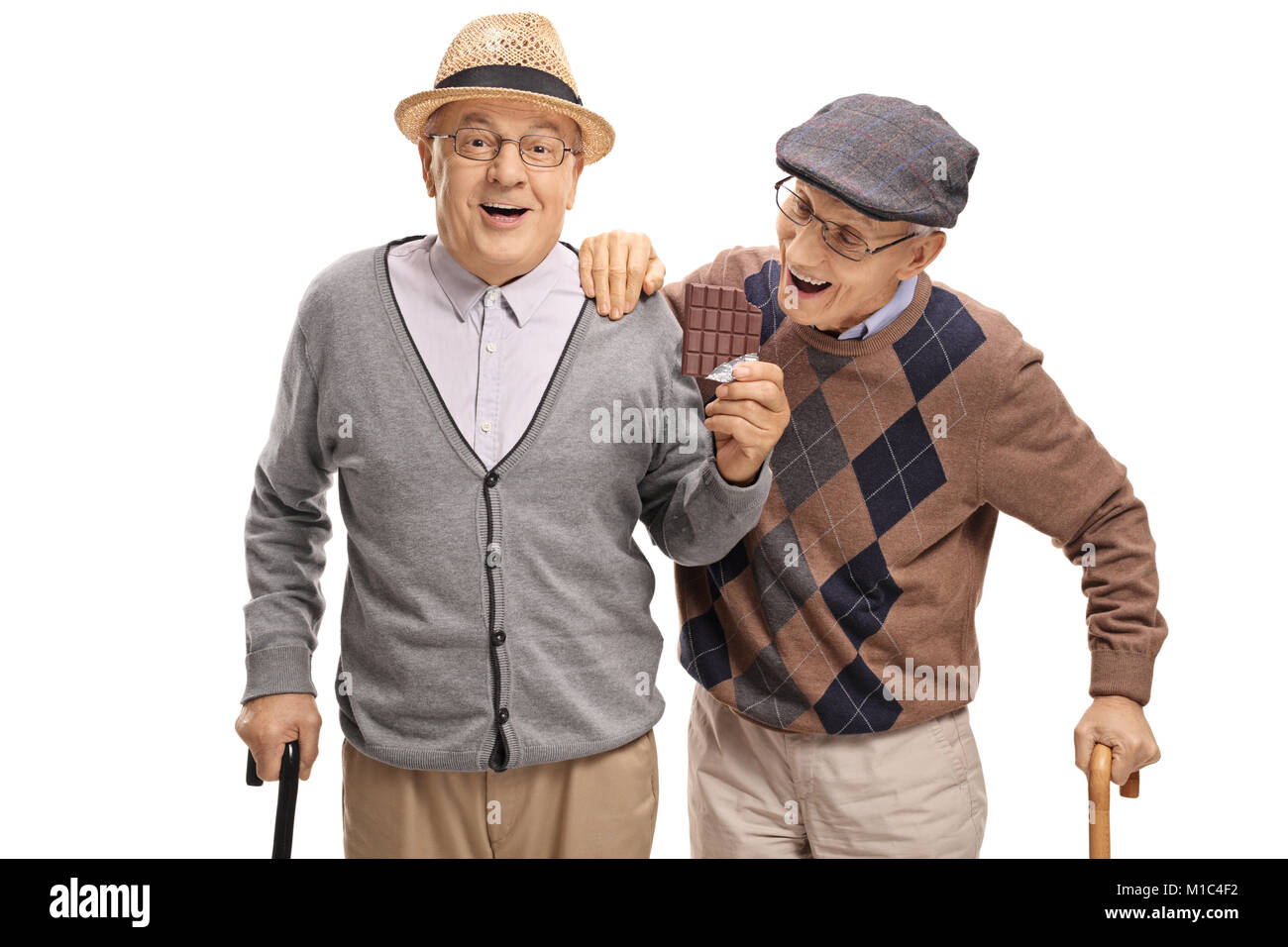 Elderly man sneaking up on another elderly man to grab a bite of his chocolate isolated on white background - Stock Image