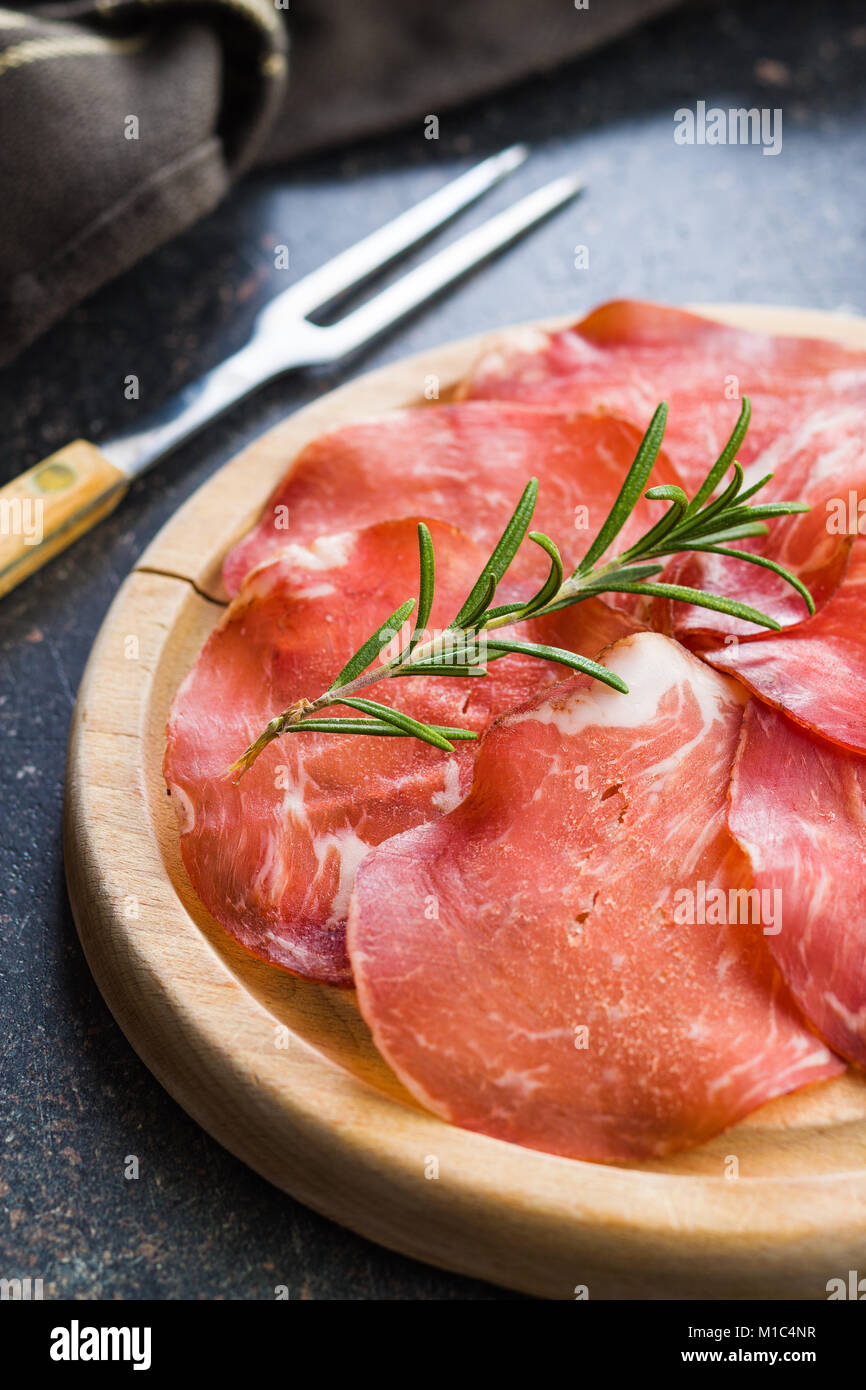 Sliced prosciutto crudo on cutting board. - Stock Image