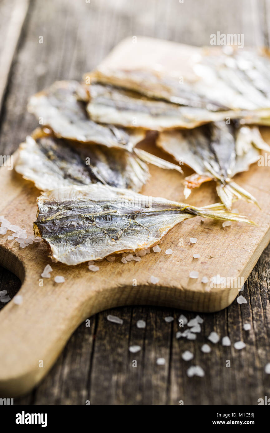 Dried salted fish on old wooden table. - Stock Image