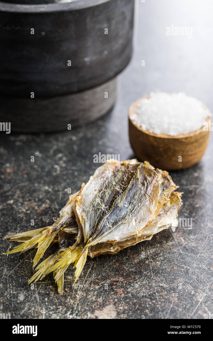 Dried salted fish on old kitchen table. - Stock Image