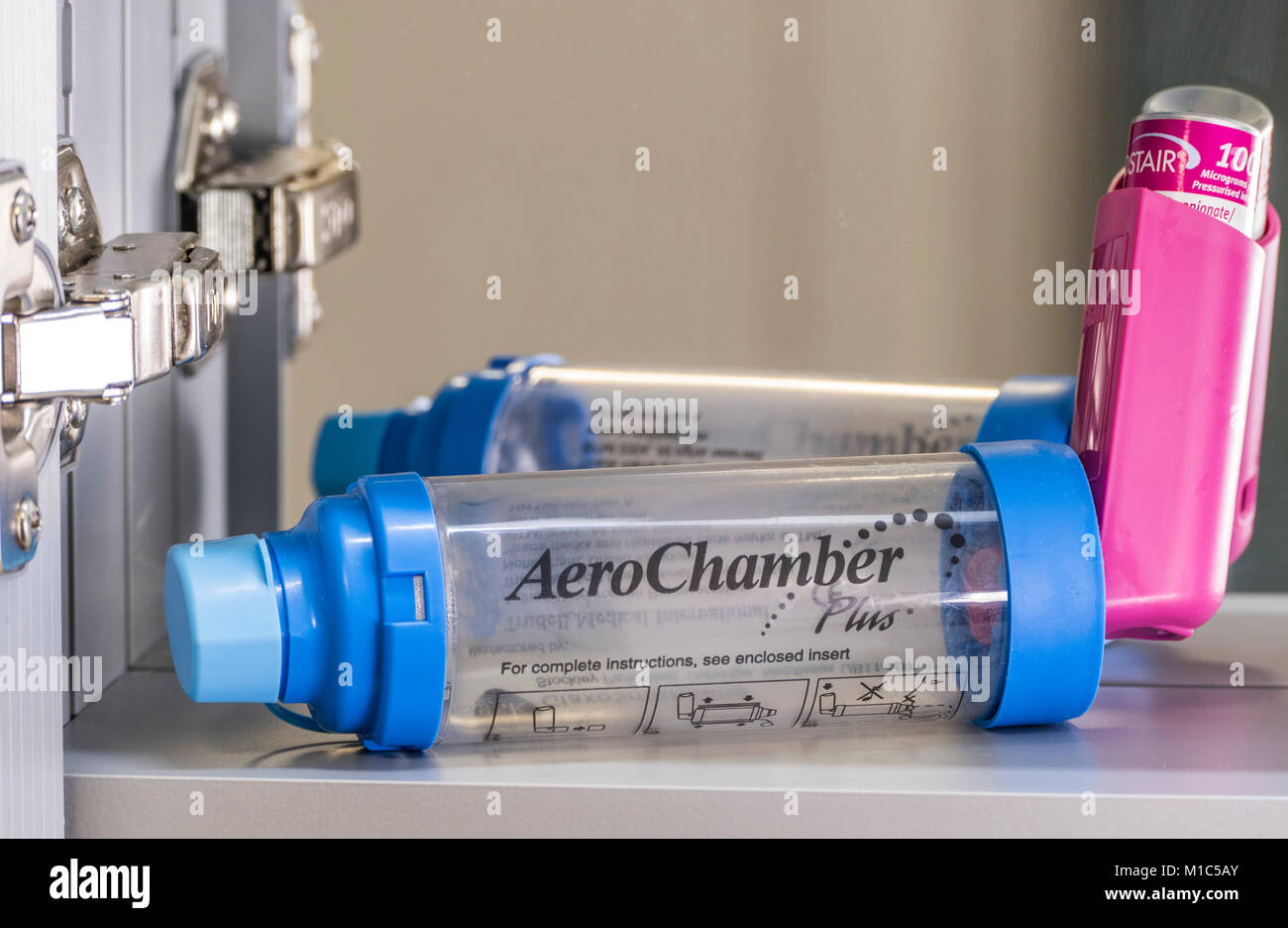 An AeroChamber Plus inhaler / puffer in a bathroom cabinet, ready to deliver a metered dose of asthma medication - Stock Image