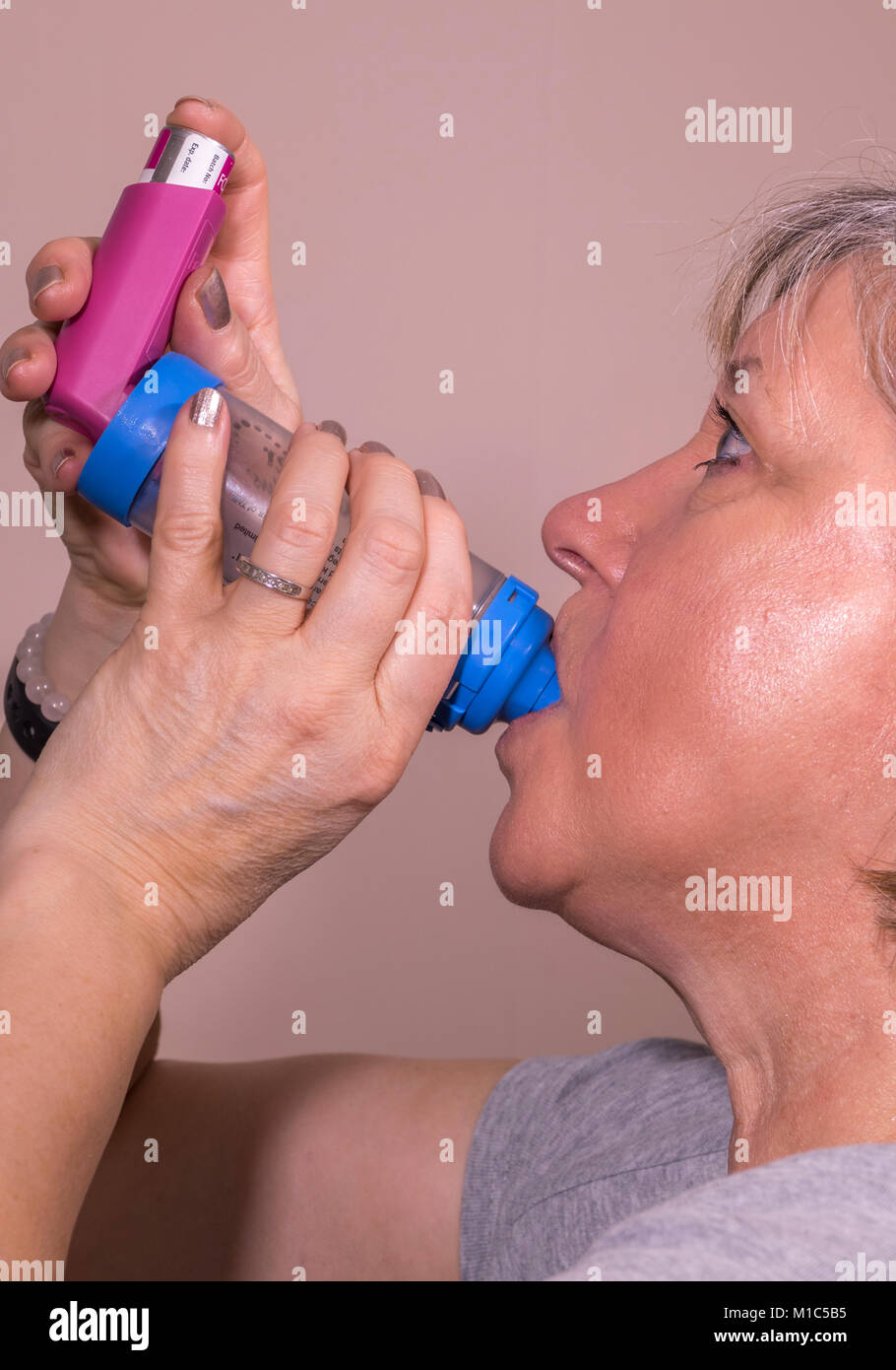 A caucasian woman in her fifties, using an AeroChamber Plus inhaler / puffer to deliver a metered dose of asthma - Stock Image