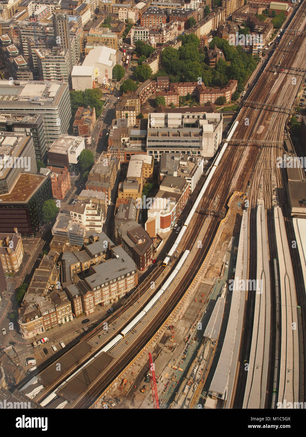 A view looking down from the top viewing floor of The Shard, London, to the train tracks and trains coming into - Stock Image