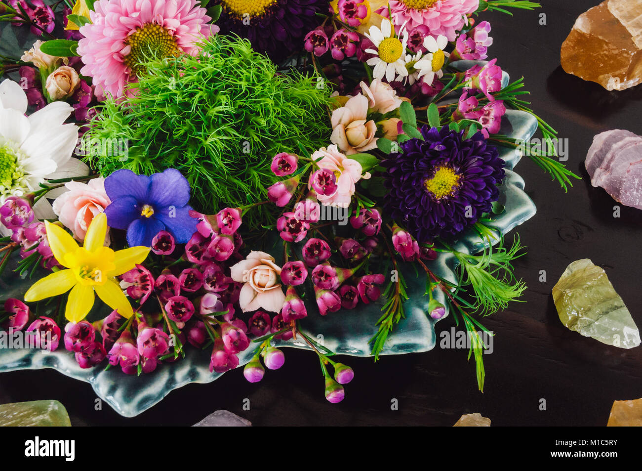 Assorted Spring Flowers on Dark Table with Honey Calcite, Amethyst and Green Calcite Stock Photo