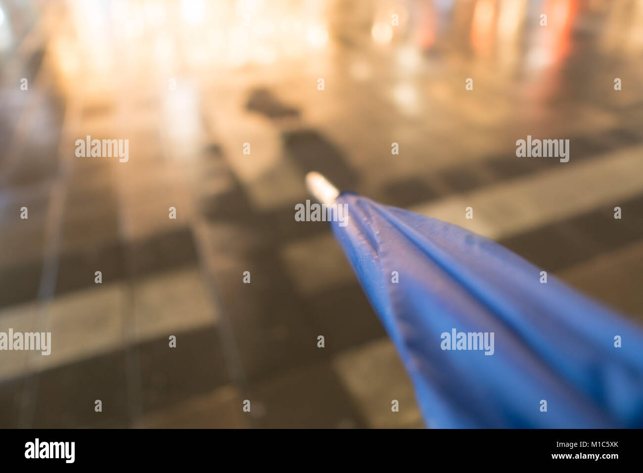 Blurred umbrella with wet stone pavement in the background during night time with nice light reflections - Stock Image