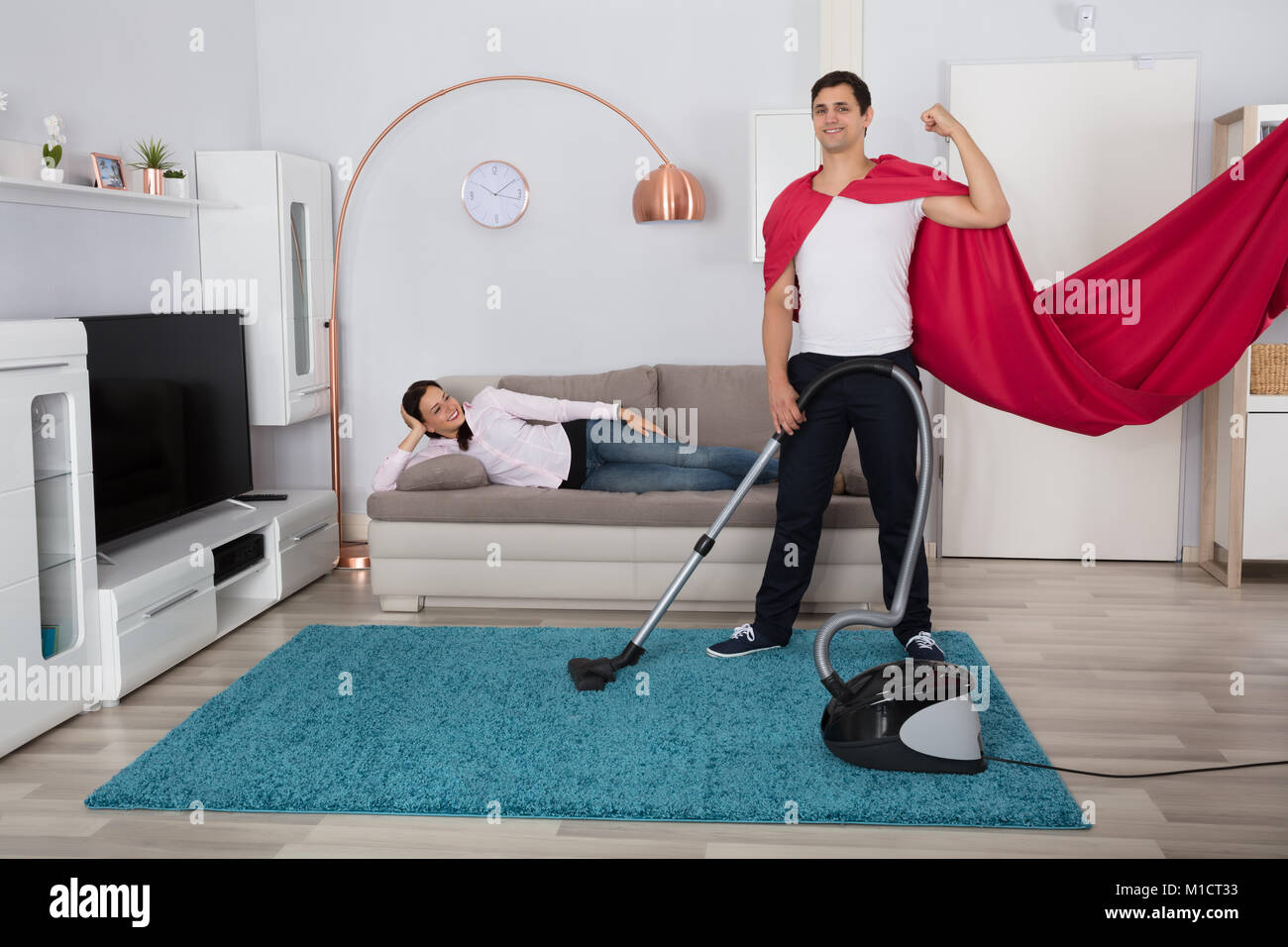 Happy Woman Lying On Sofa Looking At Her Husband Cleaning Carpet