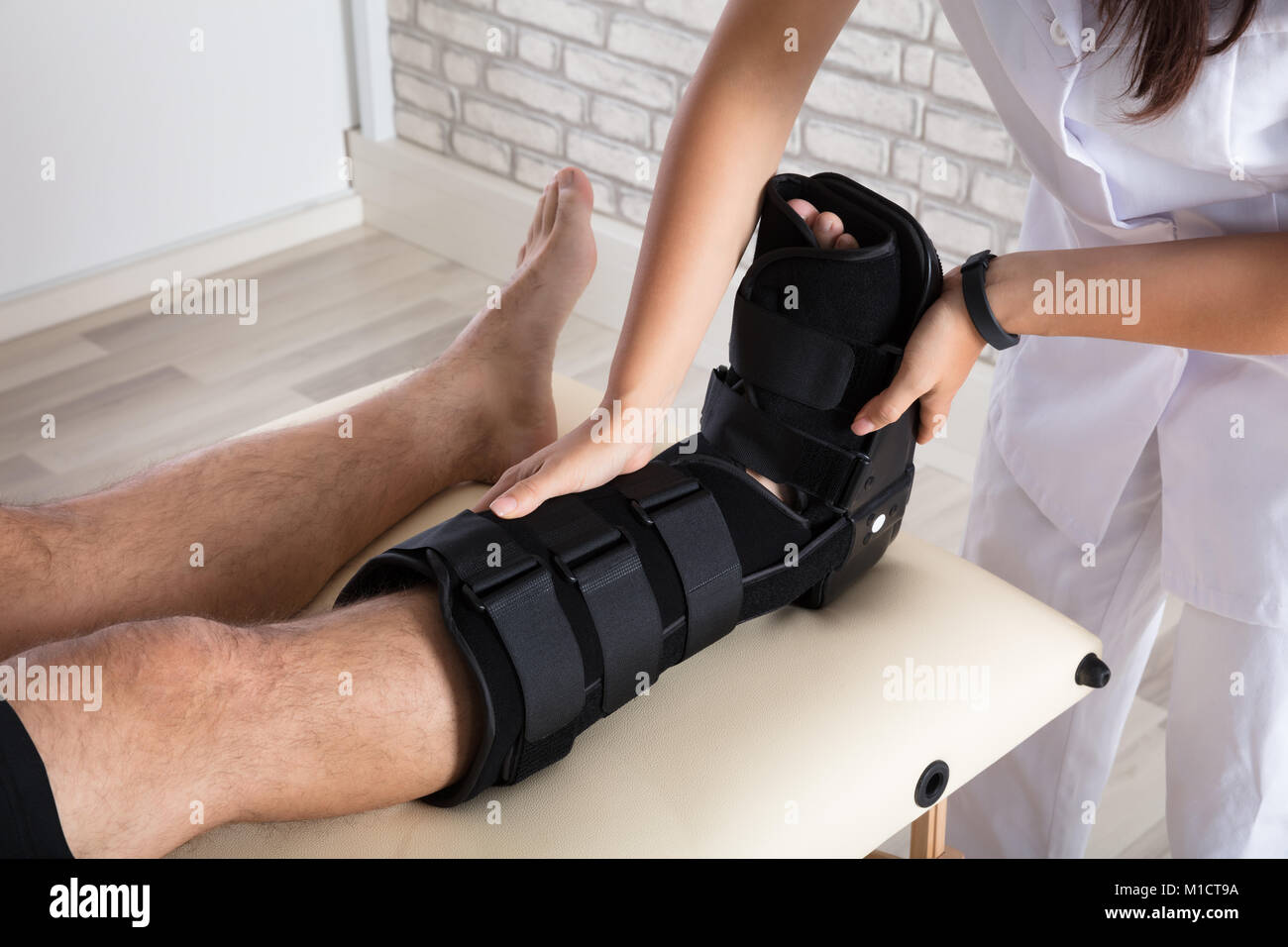 Close-up Of A Orthopedist Putting Walking Brace To Patient's Leg - Stock Image