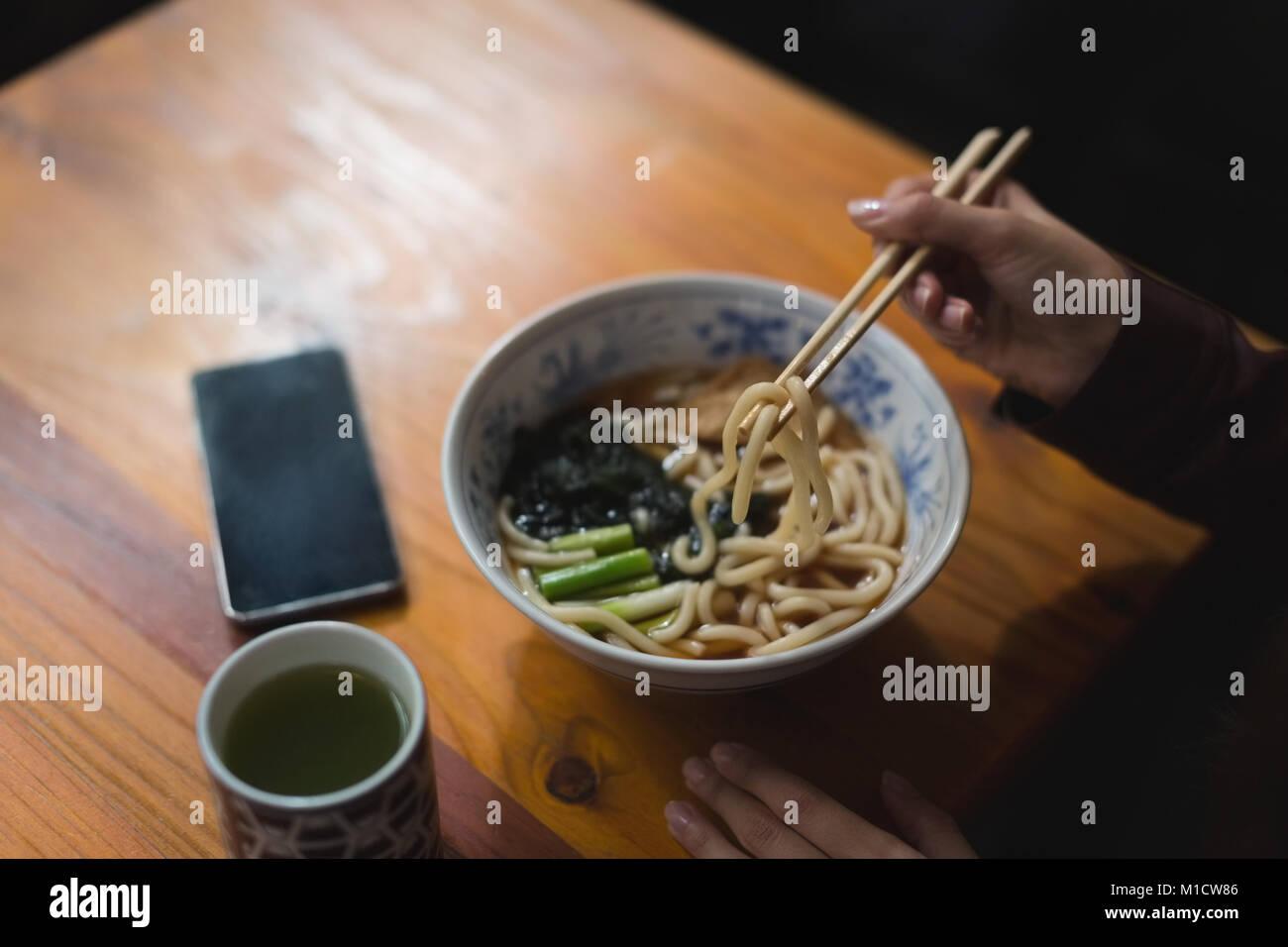 Woman having noodles in restaurant - Stock Image