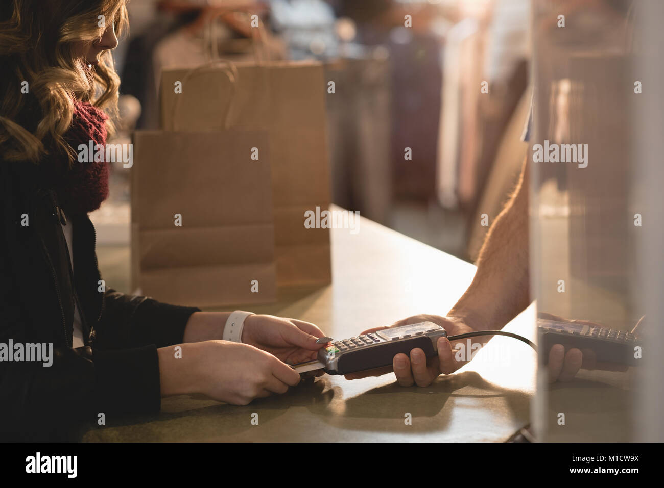 Woman making payment through mobile phone - Stock Image