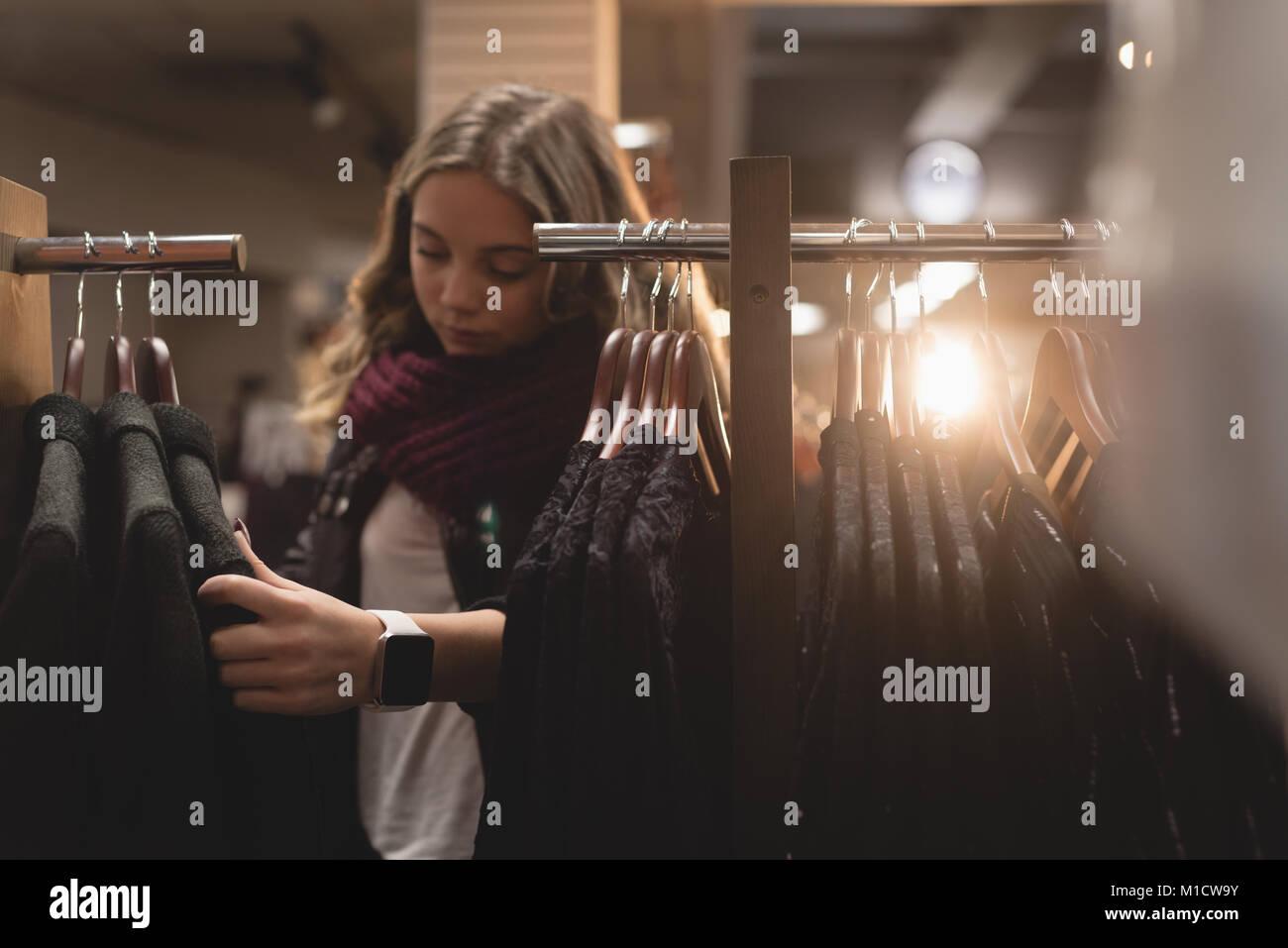 Beautiful woman selecting dress from rack - Stock Image