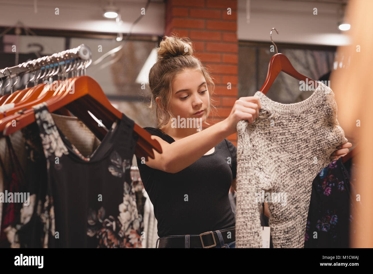 Beautiful woman selecting clothes from rack - Stock Image