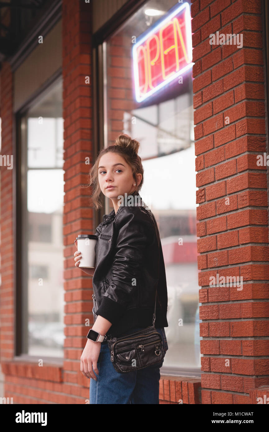 Thoughtful woman standing with disposable glass - Stock Image