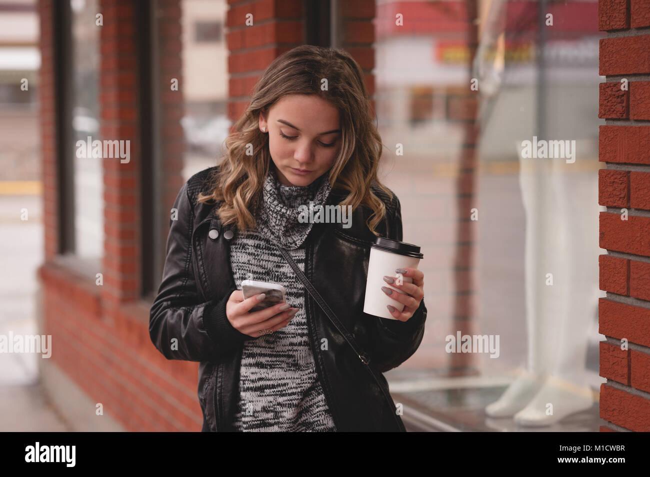 Beautiful girl using mobile while having coffee Stock Photo