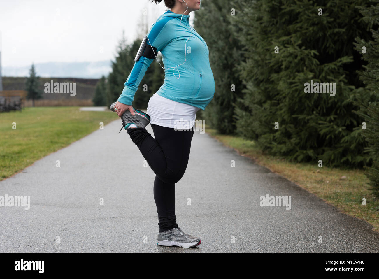 Pregnant woman performing stretching exercising - Stock Image
