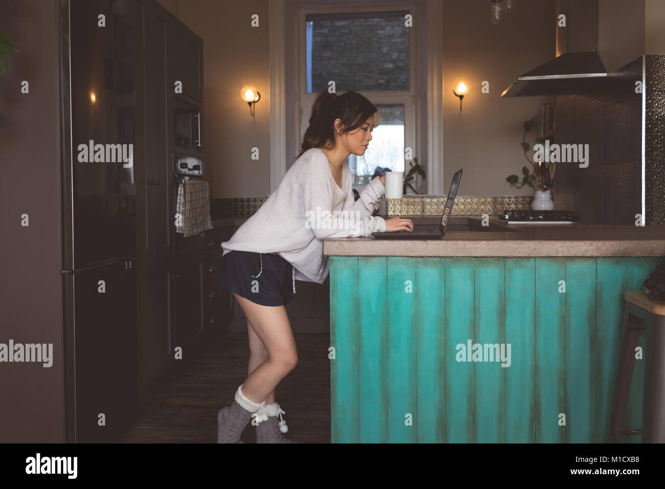 Woman using laptop at home - Stock Image