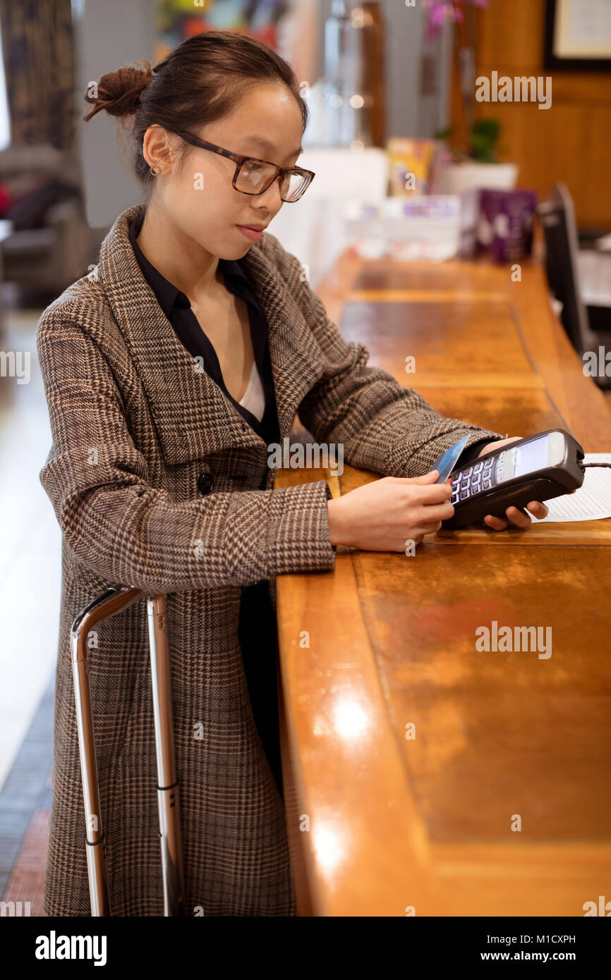 Woman swiping his card on payment terminal machine - Stock Image