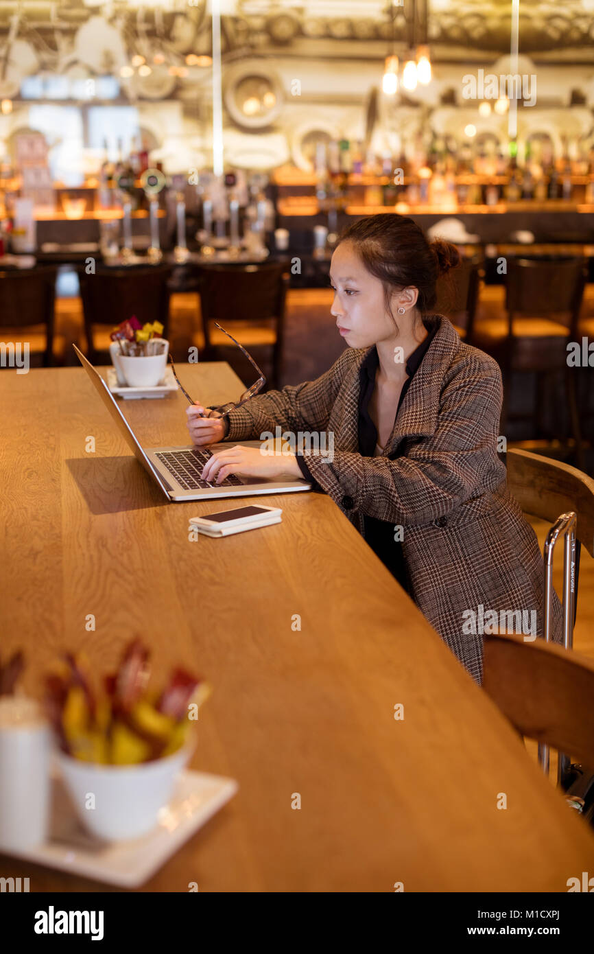 Female executive using laptop at table - Stock Image